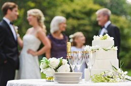 Wedding table with champagne and cake, people in background