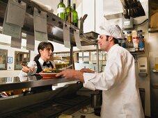 Waitress gesturing to chef in restaurant kitchen