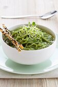 Green spaghetti in vegetable stock with grissini