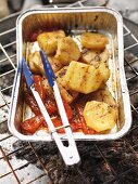 Barbecued potatoes and peppers in an aluminium tray on the barbecue