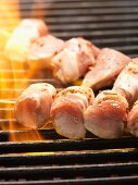Skewers of pork fillet wrapped in bacon on the barbecue