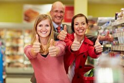Germany, Cologne, Man and women showing thumbs up in supermarket