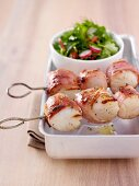 Scallops wrapped in bacon on a skewer and a side of salad