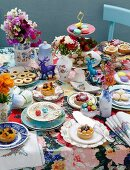 A plentiful array of cakes with a colourful display of flowers