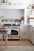 Vintage cooker below masonry extractor hood in white, country-house kitchen