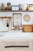 Kitchen sink below kitchen utensils hanging on wall and various vessels on shelf