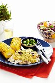 Chicken in Pipián sauce with barbecued corn on the cob