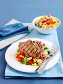 Grilled pork steaks with sweetcorn and vegetable salad