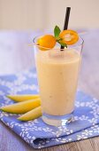 An exotic smoothie with mango and kumquats on a blue napkin on a wooden tabletop
