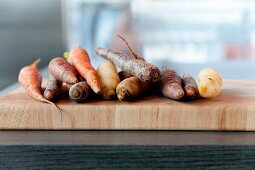 Carrots of assorted colours on a chopping board