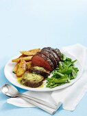 Fillet of beef with anchovy butter, roast potatoes and peas