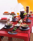 Asian place settings with floral decorations on a red table with red bamboo table runners