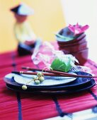 An Asian place setting with duckweed and chopsticks on a red bamboo table runner
