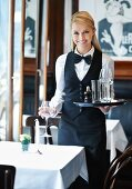 A waitress setting out glasses at a pub