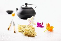 Egg noodles, chopsticks, a teapot and orchid flowers