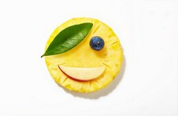 A pirate face made from pineapple, apple, a blueberry and a leaf