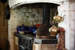 Blue enamel cooking pots on a rustic stove in a simple country house