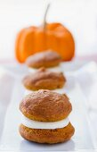 Three Mini Pumpkin Whoopie Pies on a White Platter with a Pumpkin in the Background