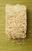 Chinese egg noodles on a bamboo mat
