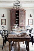 Place settings on antique table and retro-style chairs in front of farmhouse cupboard in elegant, rustic dining room