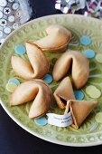 Fortune cookies with rice paper confetti on a plate
