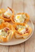 Filo pastry cases filled with prosciutto, quail's eggs and hollandaise sauce