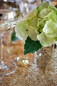 A glass of wine and a hydrangea on a table