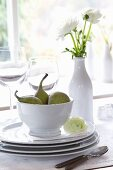 A stack of crockery with figs and a vase of white ranunculus flowers