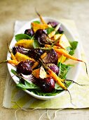 Warm root vegetable salad made with carrots, pumpkin, beetroot and onions