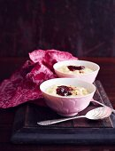 Two bowls of creamy rice pudding with strawberry jam and cinnamon