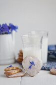 Milk with heart-shaped cinnamon biscuits with sugar glaze and cornflower petals