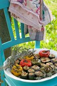 Stuffed vegetables (peppers, courgettes, onions, aubergines) on a wooden chair in the garden