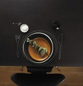 Gedeck auf Kreidetafel mit Holzteller, Salz und Weinglas