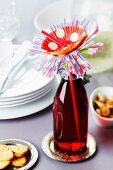 Drink in bottle with drinking straw and flower made from paper cake cases