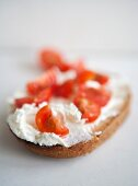 A slice of bread topped with cream cheese and tomatoes