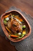Stuffed chicken with vegetables in a clay pot
