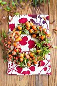 Wreath of various rosehips and branches of spirea leaves in autumnal colouring