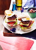 Mini bacon cheese burgers with vegetables, onions, fried quail's eggs and Australian flags