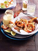 Grilled prawns with spicy mayonnaise and limes on a wooden table