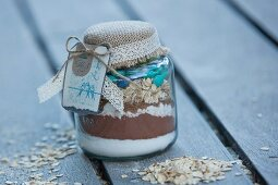 Dry ingredients for making mocha and oat biscuits, in a jar as a gift