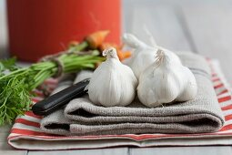 Garlic bulbs and baby carrots on a tea towel