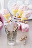 Marshmallows shaped like ice cream cones on skewers with mottoes on clothes pegs