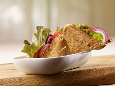 Wholegrain bread sandwich filled with batavia lettuce, onion rings and tomatoes