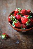 Frische Erdbeeren; daneben eine angebissene Erdbeere
