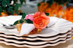 Serviette with roses as a serviette ring on stacked plates