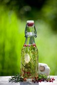 Herb-infused oil in a bottle on a wooden board in the garden