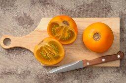 Fresh naranjillas on a chopping board with a knife