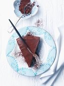 A slice of chocolate cake with cocoa powder