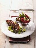 Veal kebabs on vegetables with a green salad