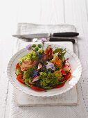 Colorful salad plate with edible flowers and bacon